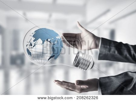 Cropped image of business woman hands holding lightbulb with Earth globe inside with office view on background. Elements of this image are furnished by NASA. Mixed media.