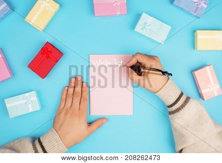Top view of hands writing a wish list on a blue background.