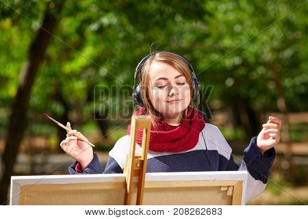 Beautiful girl draws on an easel and listens to music with closed eyes