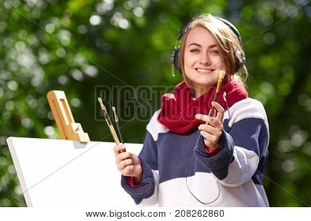Beautiful girl on a background of green trees smiling listening to music and showing brushes that draws