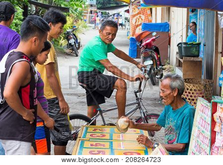 Dauin Philippines - 9 September 2017: People gamble on village street. Filippino villagers look at gambling game with dice and number cards. Sweepstake game playing. Old man with dice. Guess game