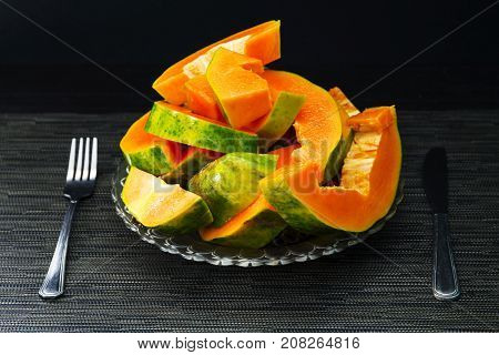 Papaya cut pieces in plate with fork and knight on black background. Cut papaya on plate served for vegetarian breakfast. Healthy and sweet tropical fruit photo. Exotic fruit with juicy orange flesh
