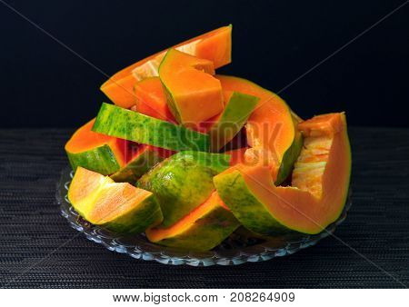 Papaya cut on black background. Cut papaya on plate served for vegetarian breakfast. Healthy and sweet tropical fruit. Exotic fruit with juicy orange flesh and green skin. Fresh papaya juice cooking