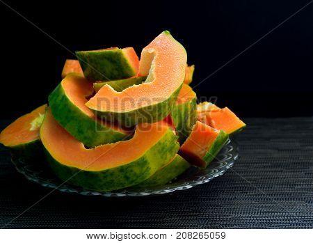 Fresh papaya cut on black background. Cut papaya on plate served for vegetarian breakfast. Healthy and sweet tropical fruit. Exotic fruit with juicy orange flesh and green skin. Ripe papaya for snack