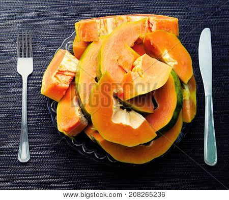 Papaya cut pieces in plate with fork and knight on black background. Cut papaya on plate top view. Vegetarian breakfast. Healthy and sweet tropical fruit photo. Exotic fruit with juicy orange flesh