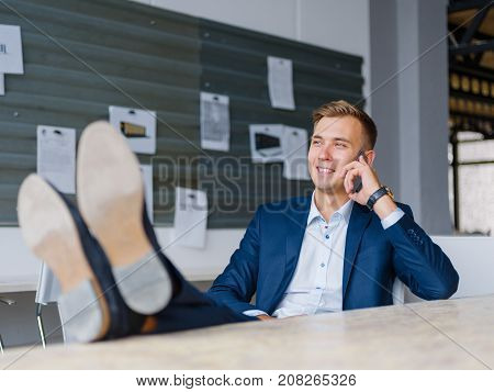 Successful and handsome business in new classy shoes man talking on a mobile phone on a blurred office background. Copy space.
