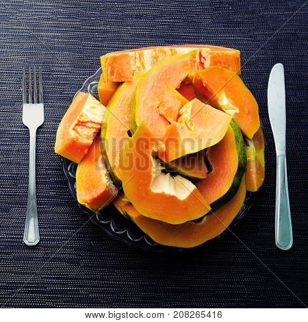 Papaya cut pieces in plate with fork and knight on black background. Papaya on plate served for vegetarian breakfast. Healthy and sweet tropical fruit. Ripe raw papaya for snack. Exotic fruit for diet