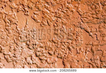 Rough red painted concrete wall. Bright rough plaster photo texture. Shabby chic backdrop. Old concrete surface with stains. Distressed texture in warm shades. Obsolete concrete wall top view