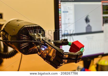 Mechanical Hand Holds a Red Cube in Research Laboratory. Machine Learning Concept. Blurred Computer Screen at the Background.