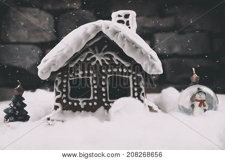 Snowy Gingerbread house with snowflakes christmas tree and globe on stone wall background. Homemade christmas cookies - gingerbread on snow background. Closeup xmas gingerbread cottage in wintertime