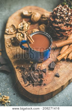 Rich winter hot chocolate with cinnamon and walnuts in blue enamel mug on wooden board over grey concrete background, selective focus