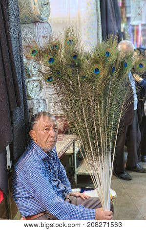 Fars Province Shiraz Iran - 19 april 2017: One unknown elderly Iranian man sells peacock feathers at the Vakil bazaar.