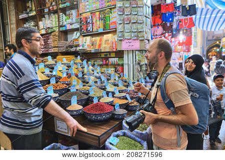 Fars Province Shiraz Iran - 19 april 2017: The Iranian seller of spices and dried fruits helps the tourist to choose the goods for purchase.