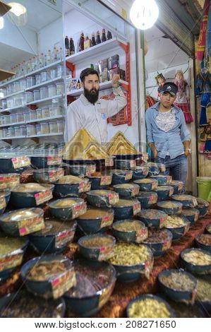 Fars Province Shiraz Iran - 19 april 2017: Two sellers of oriental sweets are bored waiting for buyers.