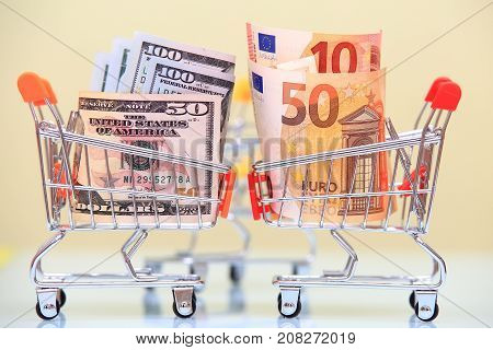 Currency rate concept. Euro and dollar currency in shopping carts opposite each other.