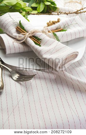 elegant place setting white and gold with garland of green leaves