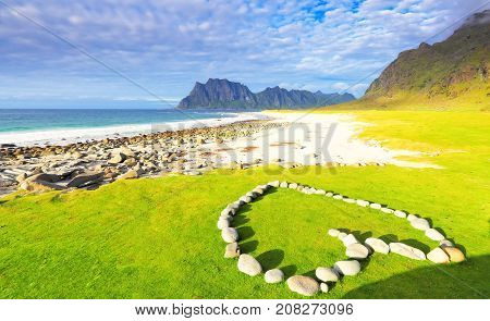 Romantic beach at the sunset. White stones laying in heart form on green grass. Famous Uttakleiv beach on the Lofoten islands.