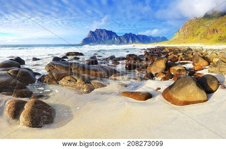 Norway beach with white sand and stones at the sunset. Summer evening at the Lofoten islands.