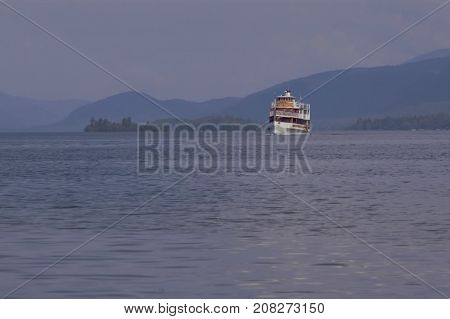 A large boat on the horizon in front of the mountains