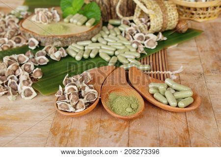 Moringa capsule for health on wood background