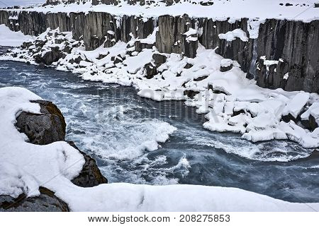 Cold rough river in the frozen rocky canyon in Iceland. Horizontal.
