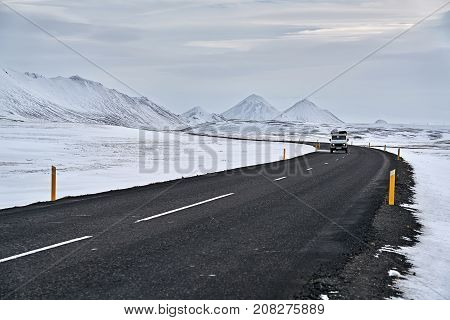 Roadway with orange roadside pillars between the snow fields and snow mountains on the background of the cloudy sky in Iceland. There is a car on the driveway. Horizontal.