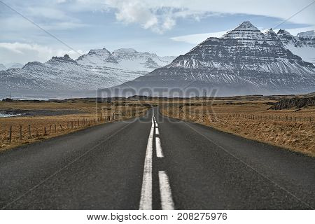 Suburban roadway between the brown fields with rocks on the background of the snow mountains and cloudy sky in Iceland. Horizontal.