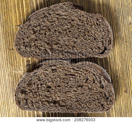 two pieces of black rye bread, lying on a wooden board. photo closeup, top view