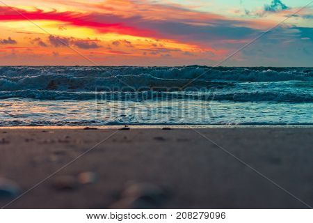 selective focus of the beach shore and colorful sky at sunrise on a windy morning