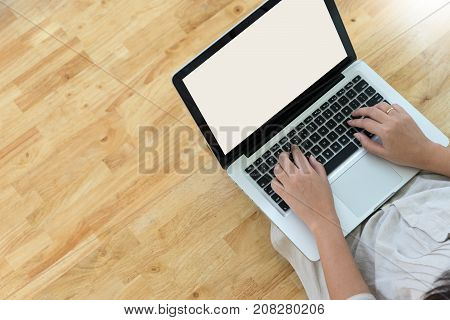 Woman Student Working On Laptop Computer On Wood Floo
