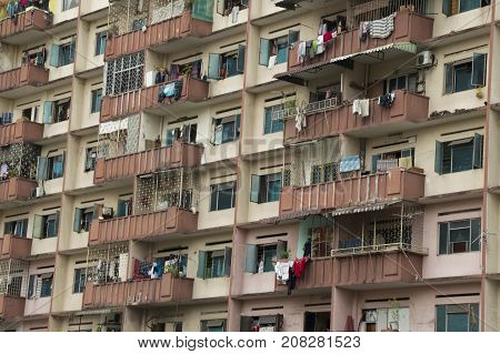 Deteriorated facade of Asian building with clothes hanging