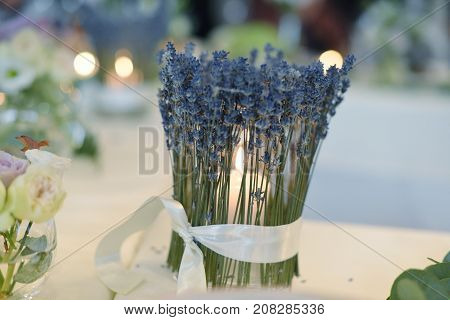candle-holder decorated with lavender burns on table