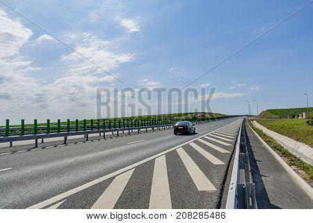 Side view highway on sunny summer day crossing vineyards in Romania near Murfatlar. Car rides on highway that runs through the vineyards. Highway traffic.