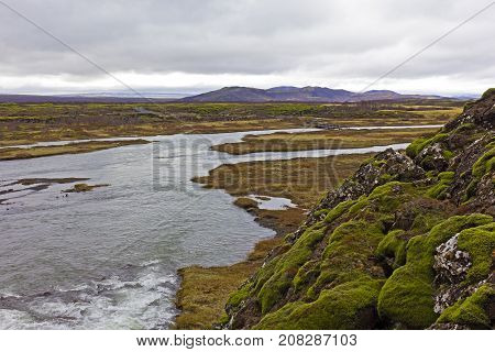 Iceland unearthly landscape. Moss-covered stones along the river.