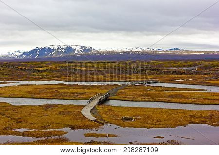 Iceland terrain in spring. Snow mountains on horizon and grassy meadows with ponds of thermal water.