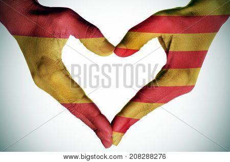 the hands of a young woman forming a heart patterned with the flags of Spain and Catalonia