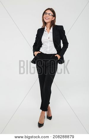 Full length portrait of a happy cheerful businesswoman in suit and eyeglasses standing with arms in pockets and laughing isolated over white background