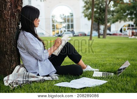 Side view of beautiful asian female student, studying in park, outdoor