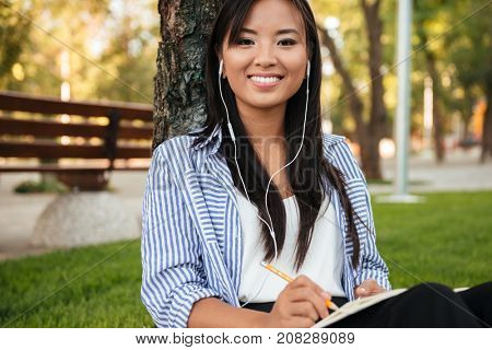Close-up of beautiful asian female student listening to music, looking at camera, outdoor