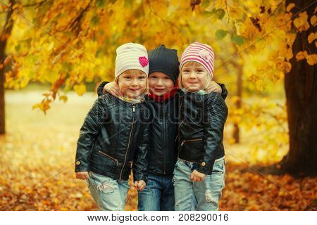Three happy friends kids hugging and laughing in autumn park.