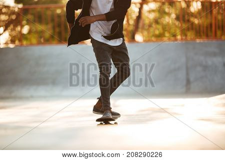 Cropped image of an african skateboarder skating on a concrete skateboarding ramp at the skate park