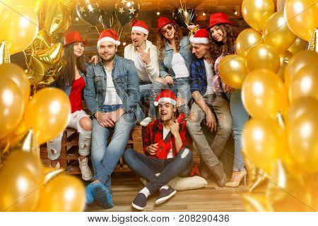 Party with group friends wearing Santa's hats. Young people, hipsters sharing good and positive mood, celebrate special occasion. Midnight at New Year's Eve party or christmas.