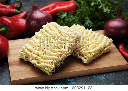 Raw asian instant noodles on wooden board