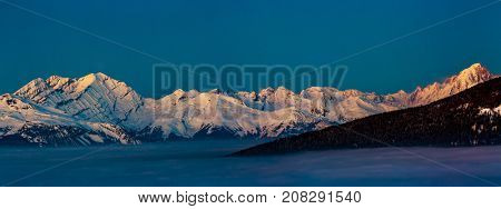 Scenic panorama night landscape of Crans-Montana range in Swiss Alps mountains with peak in background, Crans Montana, Switzerland.