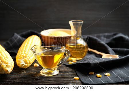 Glass gravy boat with corn oil and ripe cobs on wooden background