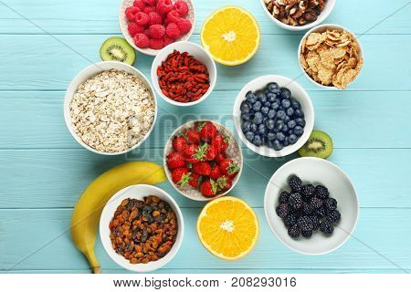 Composition with nutritious oatmeal and different ingredients for breakfast on wooden background poster