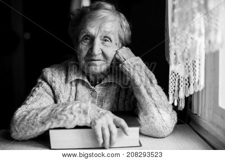 Black and white contrast portrait of an elderly woman sitting with a book.