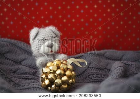 Small bear toy and Christmas jingle bells on blanket