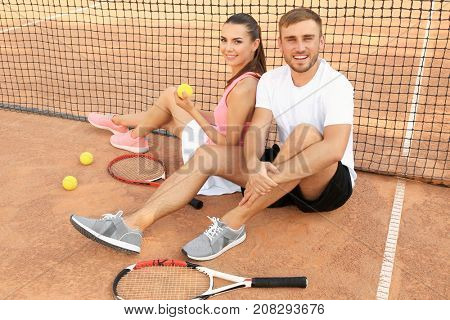 Young couple sitting near net at tennis court