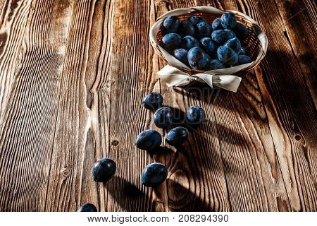 blue plum spilled on a wooden background